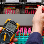 Man testing electrical current of circuit board - Electrician Sunshine Coast
