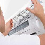 Man repairing a white air conditioner - Air Conditioner Sunshine Coast